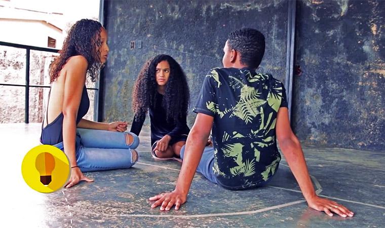 Estudante Maria Clara conversa com uma menina e um menino. Eles estão sentados no chão