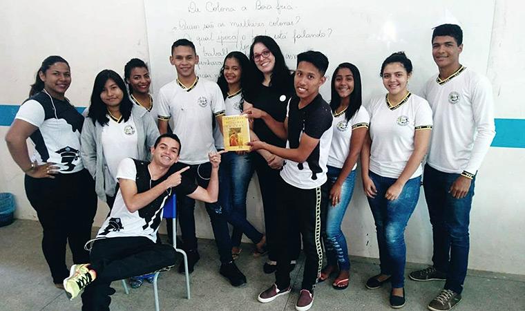 A professora Rutemara Florencio posa ao lado de seus alunos. Um deles segura o troféu do Prêmio Educador Nota 10