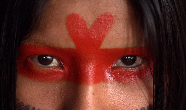 Cena aproximada de jovem indigena com o rosto pintado