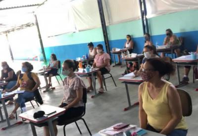Professores sentados em sala usando máscara