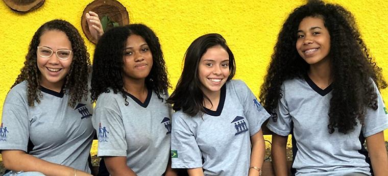 Quatro meninas integrantes do clube de leitura posam com uniforme da escola