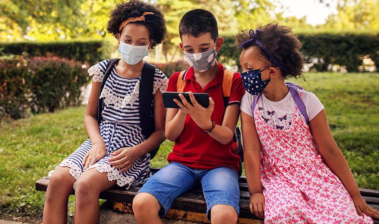 Três crianças, duas meninas e um menino sentados em um espaço como uma praça. Eles conversam e usam máscara contra covid