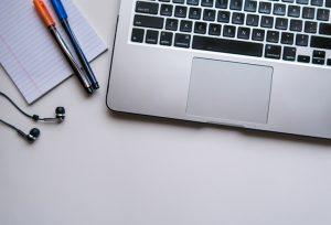 computador cinza com duas canetas e papel aparecendo