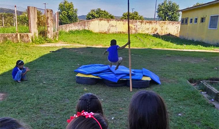 Menina segura corda e menino pula por cima e cai em colchão em atividade de salto com vara