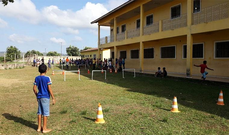 Crianças correm em campo gramado ao lado da escola em circuito que lembra barreiras de corrida