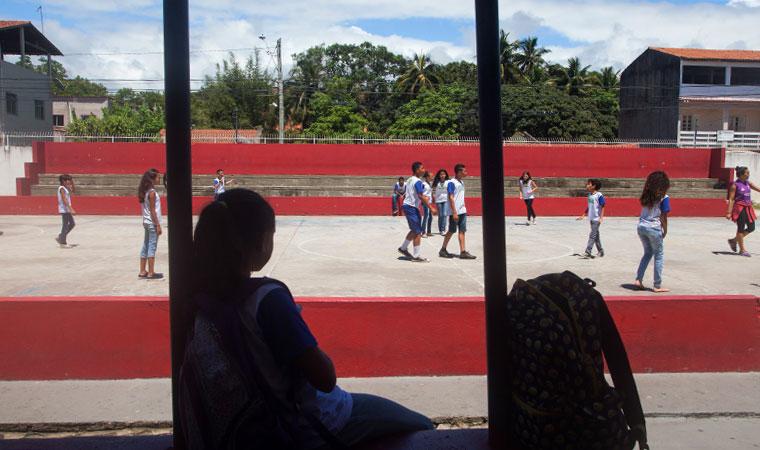 Menina observa colegas jogarem futebo em quadra da escola em dia de sol