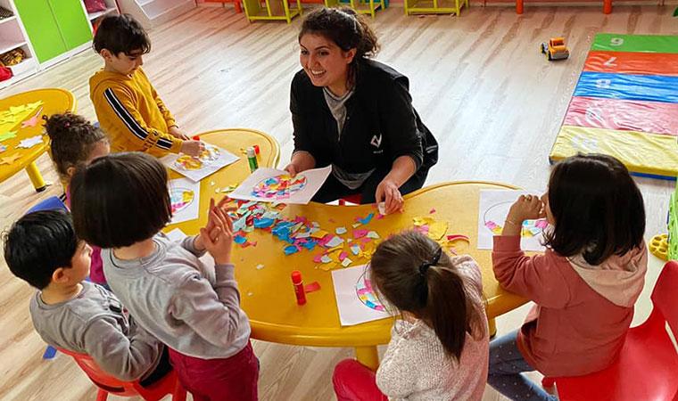 Crianças sentadas em uma mesa pequena fazem trabalho de artes